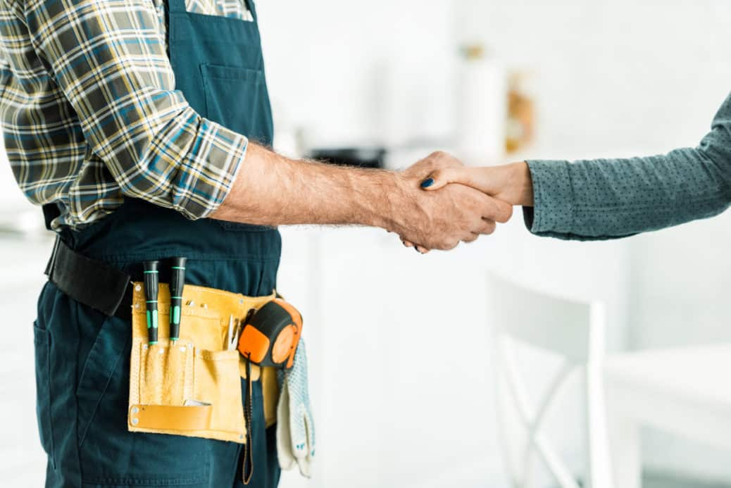plumber and client shaking hands in kitchen