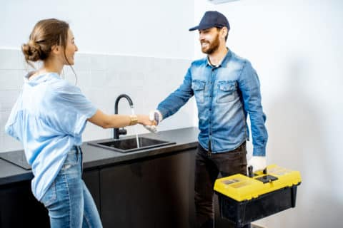 plumber shaking hands with woman, increase home value with plumbing concept