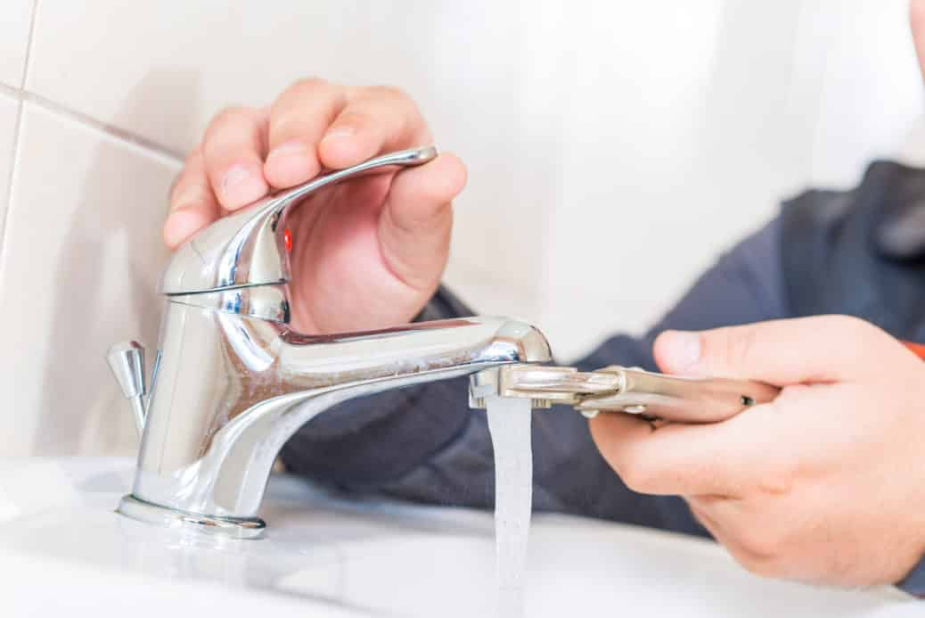 Plumber fixing faucet to lower your water bill