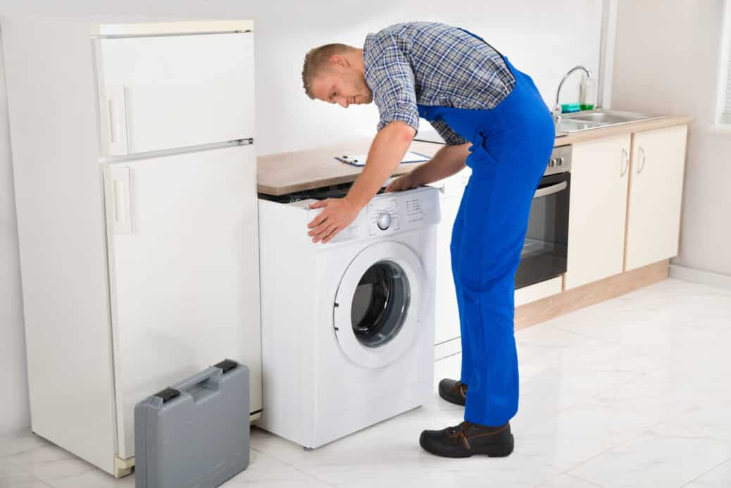 Plumber installing a washing machine, laundry room features concept